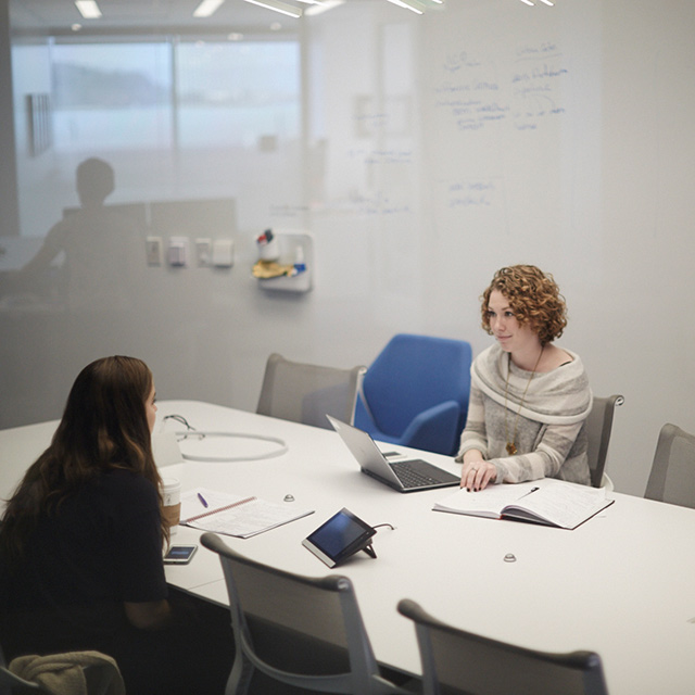 Two people sitting at a conference table.