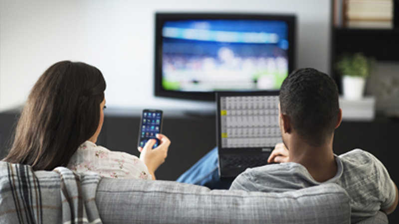 A woman using a smartphone and man using a laptop both sitting on a couch in front of a television.